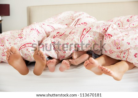 Family's Feet Poking Out From Duvet In Bed - stock photo