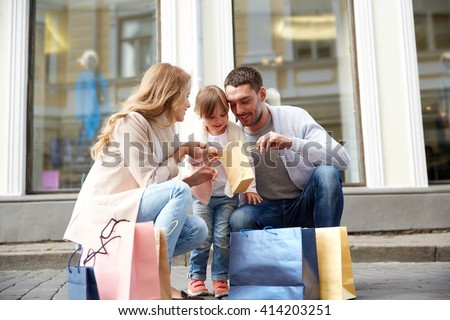 family, sale, consumerism and people concept - happy mother , father and little child with shopping bags reviewing purchases on city street - stock photo