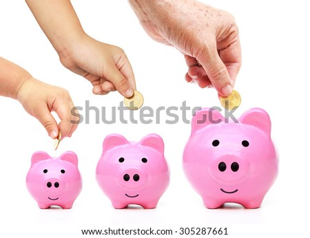 Family saving money in the pink piggy banks concept - stock photo