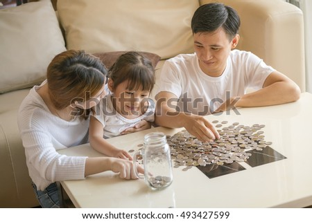 Family saving money putting coins into glass bank ,Happy Asian Family enjoying family time together, portrait of family ,Beautiful family