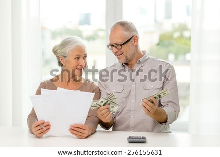 family, savings, age and people concept - smiling senior couple with papers, money and calculator at home - stock photo