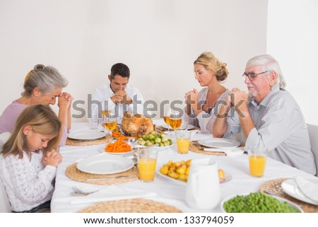 Family saying grace before eating a turkey for dinner - stock photo