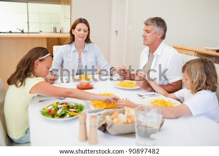 Family saying grace together - stock photo