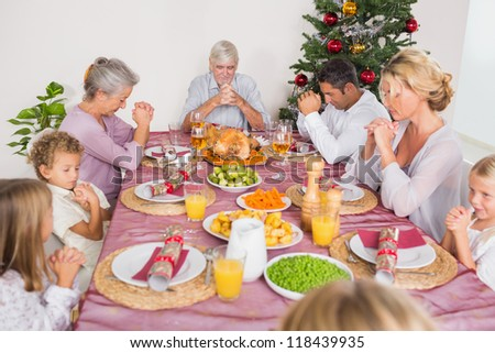 Family saying grace together before christmas dinner - stock photo