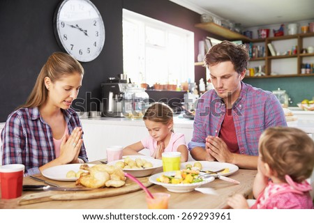 Family Saying Prayer Before Eating Meal In Kitchen Together - stock photo