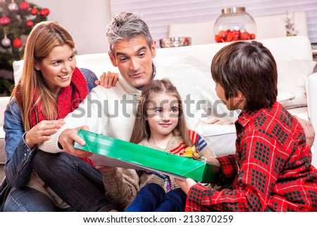 Family Scene. Parents With Children Opening Presents In Front Of Christmas Tree. - stock photo