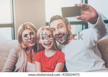 Family selfie. Happy family of three bonding to each other and smiling while father photographing them with smart phone - stock photo