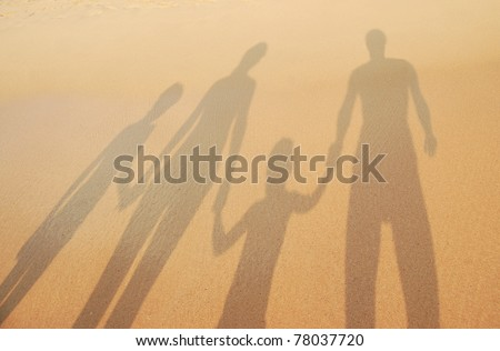 Family shadows on beach sand - stock photo