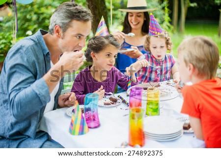 Family sharing the birthday cake. Everybody is enjoying his piece - stock photo