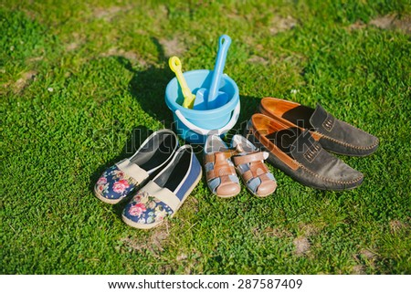 Family shoes in grass in park. Parents and child shoes. Three pairs of shoes of father, mother and son or daughter. Family, growth, love and togetherness concept. - stock photo