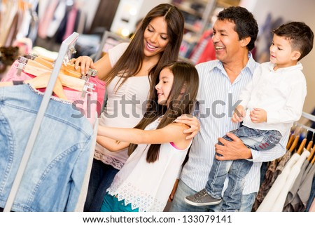 Family shopping for clothes and looking happy - stock photo