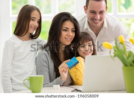 Family shopping online, two twins girls  wit father and mother enjoying in shopping  - stock photo