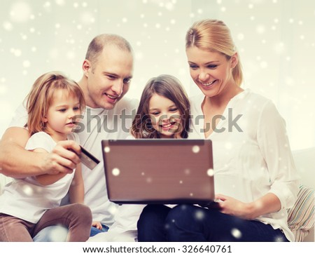 family, shopping, technology and people concept - happy family with laptop computer and credit card over snowflakes background - stock photo