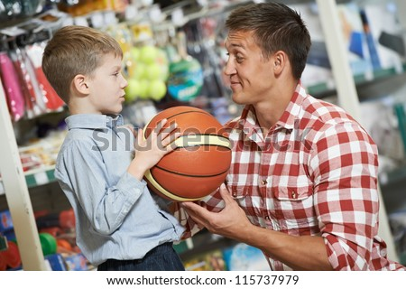 Family shopping. Young father with son choosing sport equipment basket ball at supermarket
