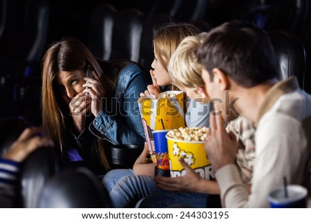 Family showing silence gesture to woman using mobilephone in cinema theater - stock photo