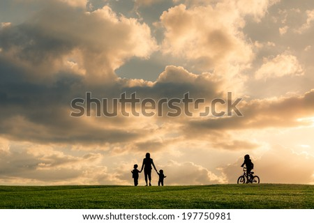 Family silhouette against a bright cloudy sky at sunset. Boy riding a bike with family walking - stock photo