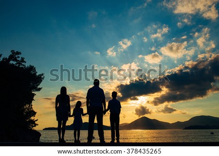 Family silhouette in the sunset - stock photo