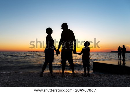 Family Silhouette. Sunset at sea. - stock photo
