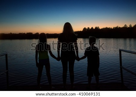 Family silhouette sunset at the lake on vacation - stock photo