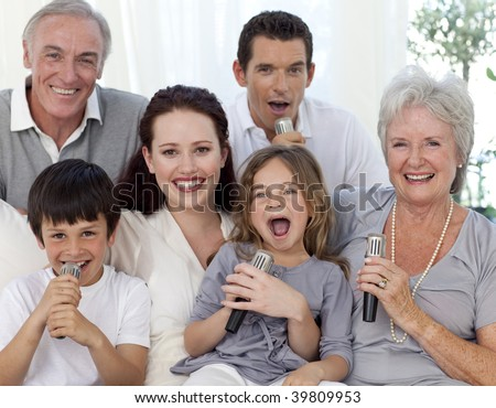 Family singing karaoke with microphones at home - stock photo