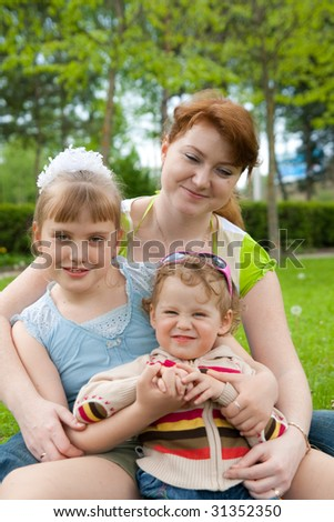family sit on green grass