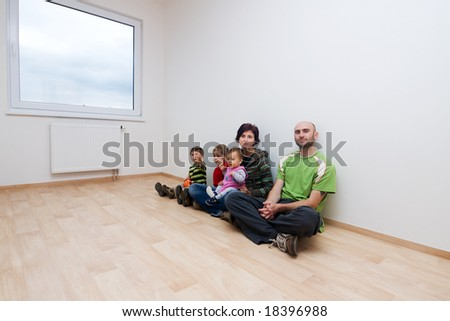 Family sitting against wall in white room of new house.