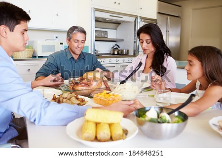 Family Sitting Around Table Saying Prayer Before Eating Meal - stock photo