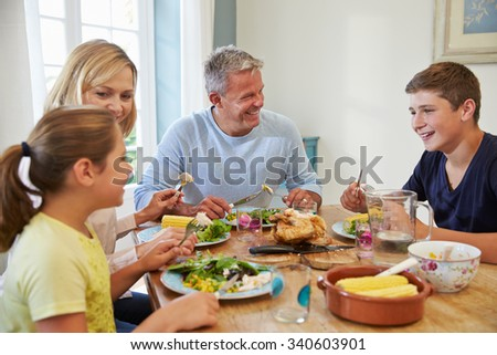 Family Sitting At Table Enjoying Meal At Home Together - stock photo