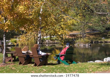 Family Sitting by a Pond in Autumn