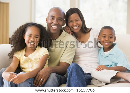 Family sitting in living room smiling - stock photo