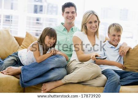 Family sitting in living room watching tv - stock photo