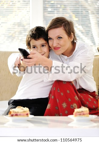 Family sitting in living room with remote control - stock photo