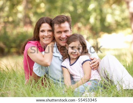 Family Sitting In Long Grass In Park - stock photo