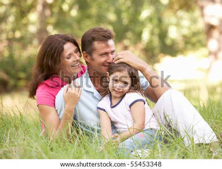 Family Sitting In Long Grass In Park