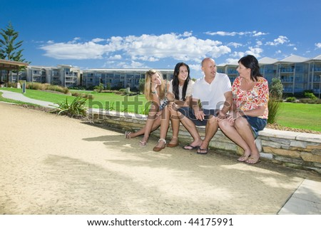 family sitting in park talking together