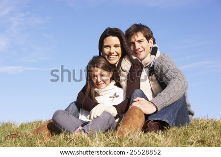 Family Sitting In Park Together - stock photo