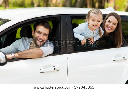 Family sitting in the car looking out windows  - stock photo