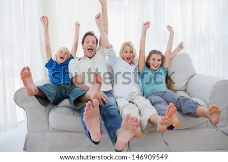 Family sitting on a couch and raising arms while watching television - stock photo