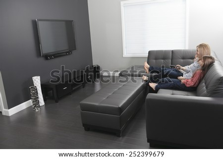 family sitting on a sofa in her living room - stock photo