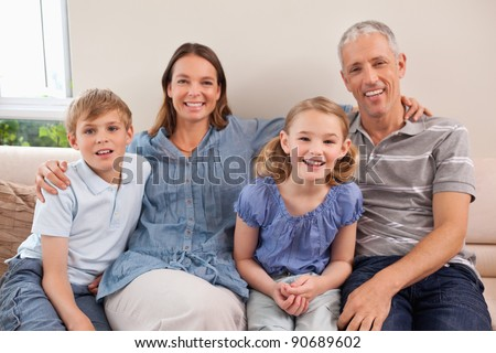 Family sitting on a sofa while looking at the camera