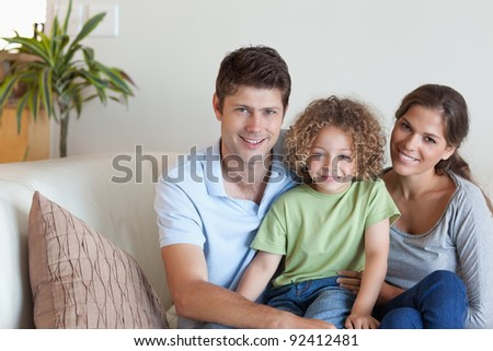 Family sitting on a sofa while looking at the camera - stock photo