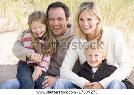 Family sitting on beach smiling - stock photo