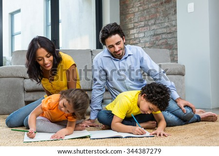 Family sitting on carpet in living room with children drawing - stock photo