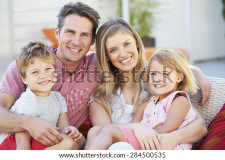 Family Sitting On Garden Seat Together