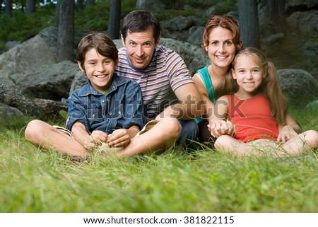 Family sitting on grass - stock photo