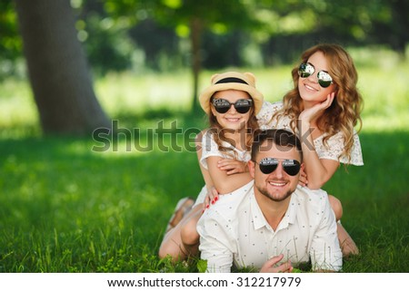 Family sitting On Grass In Park Together. Happy mother, father and daughter in the park. Portrait of happy parents and kids lying at the park