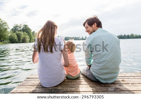 Family sitting on jetty of pond or lake in summer - stock photo