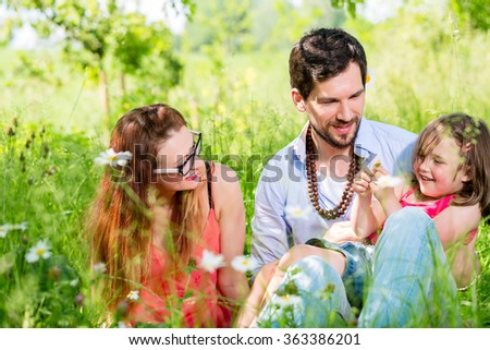 Family sitting on meadow giving their kid protection