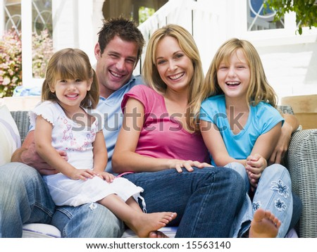 Family sitting on patio smiling - stock photo