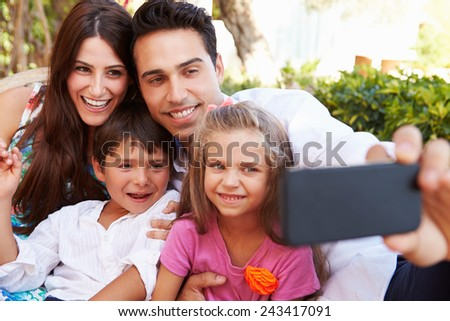 Family Sitting On Seat In Garden At Home Taking Selfie - stock photo